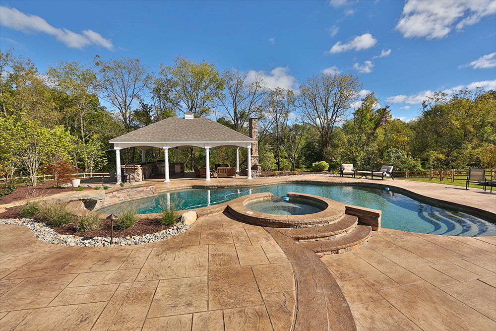 Decorative stamped concrete pool with Pennsylvania Slate pattern and outdoor fireplace