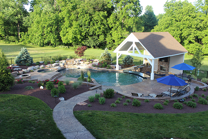 Photo of pool with stamped concrete, landscaping and boulders