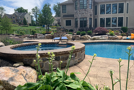 Photo of pool with decorative concrete, boulders and landscaping